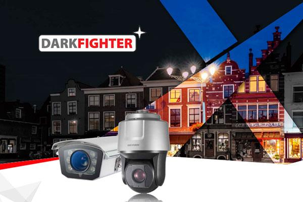 priekšplānā divas videonovērošanas kameras, fonā ēka nakts laikā ar prožektoriem, kuri to apgaismo, darkfighter logotips